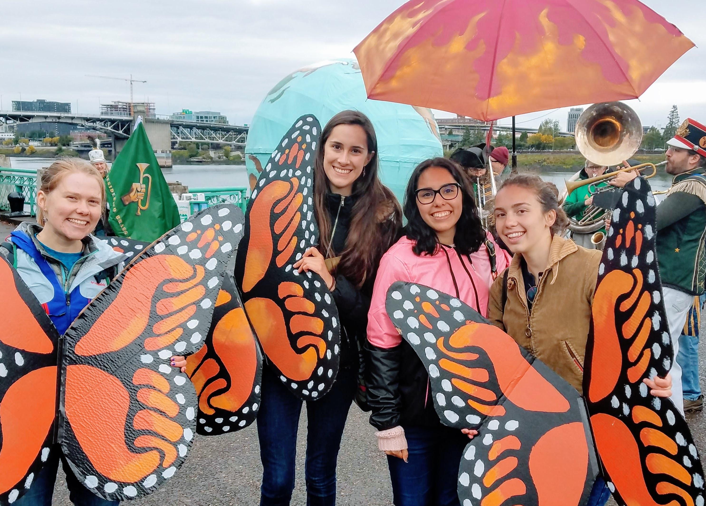 QVS fellows carrying large cardboard monarch butterflies