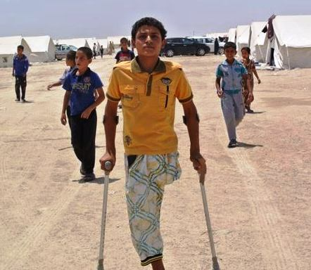 Mustafa: a young boy with one leg and arm crutches, with other boys in the background