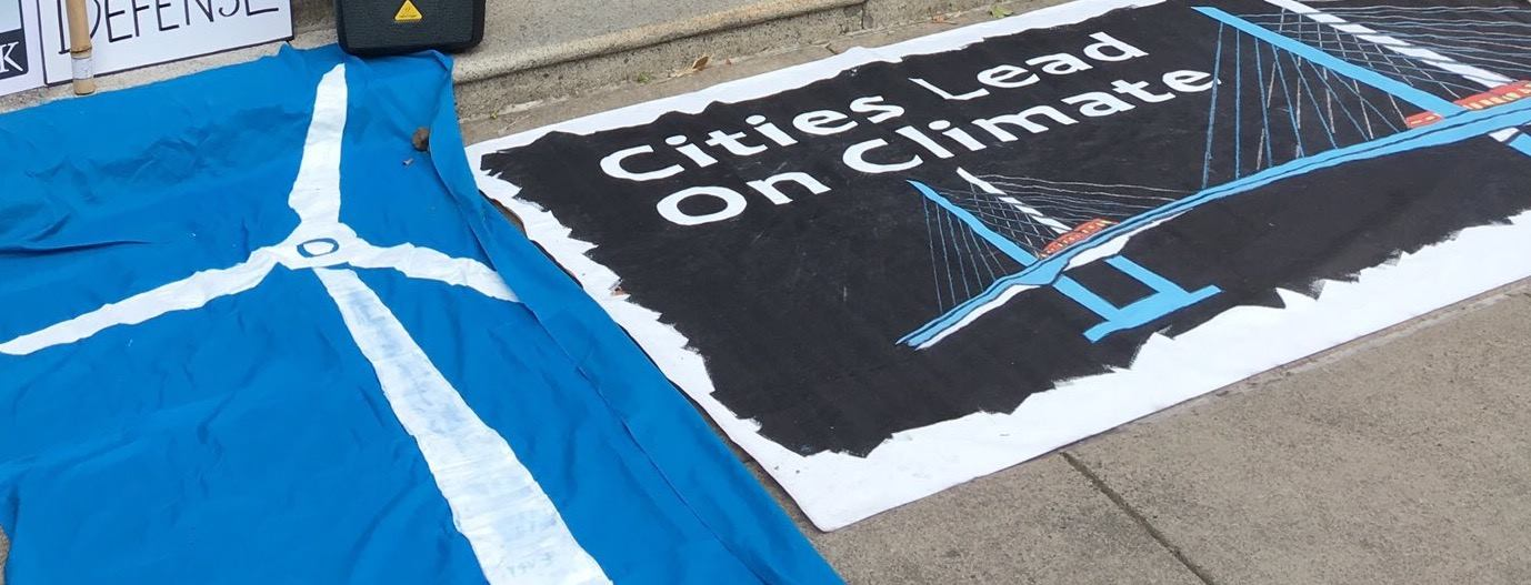 protest banner: cities lead on climate