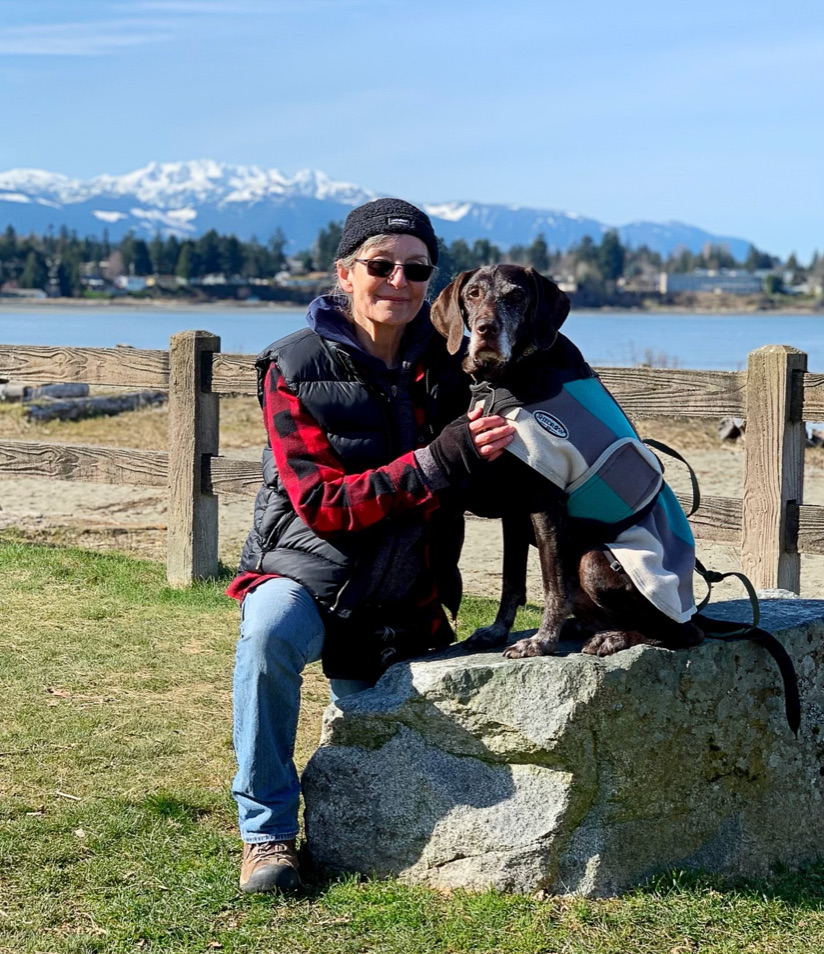 Smiling, older white woman, kneeling beside an elderly dark brown, grey faced dog, beach and mountains in the background