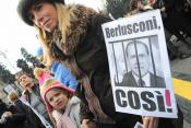 "A mother holds a placard reading ""Berlusconi, like that!"" during a demonstration"