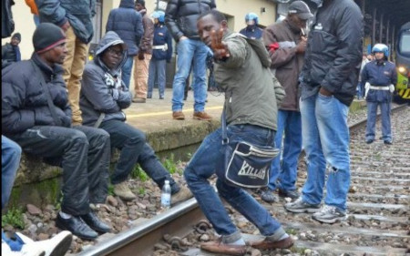 Gang of Africans rest after storming Italian train