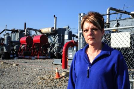 Pam Judy, PA resident, in front of a compressor station. Photo by Mark Schmerling