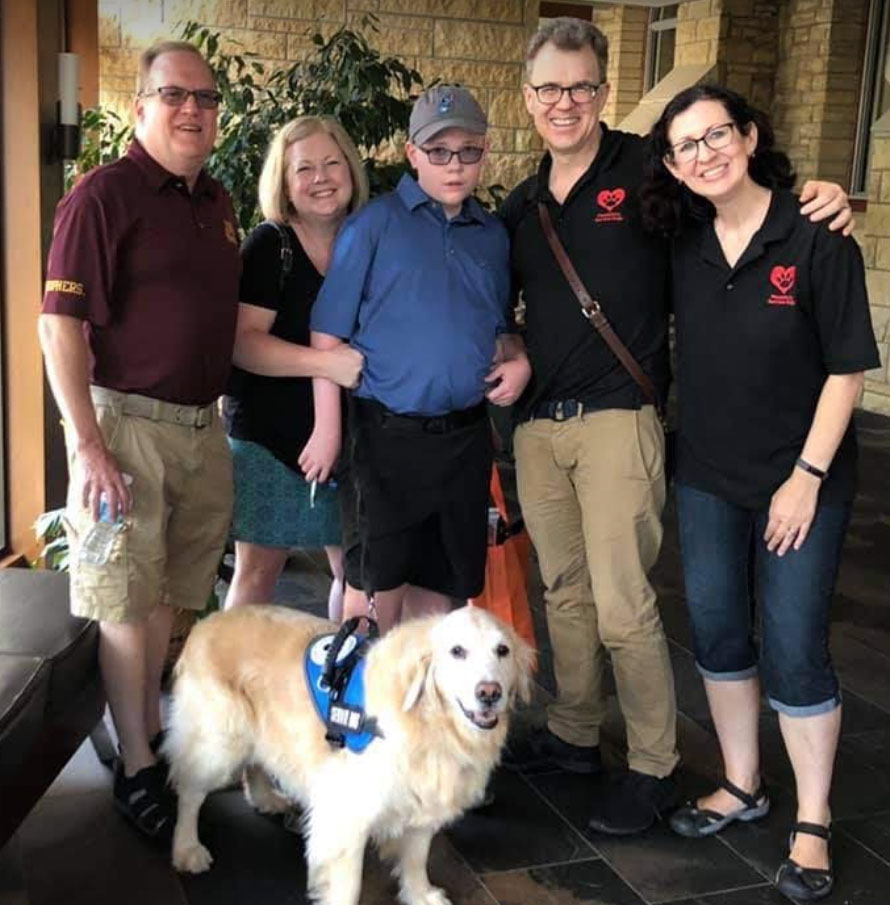 Service dog Bailey with his boy, family, and his trainers
