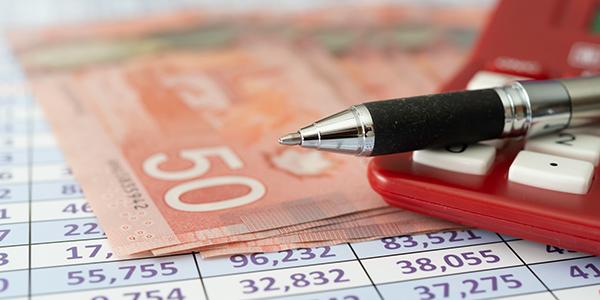De l'argent, une calculatrice et des plans financiers sur une table