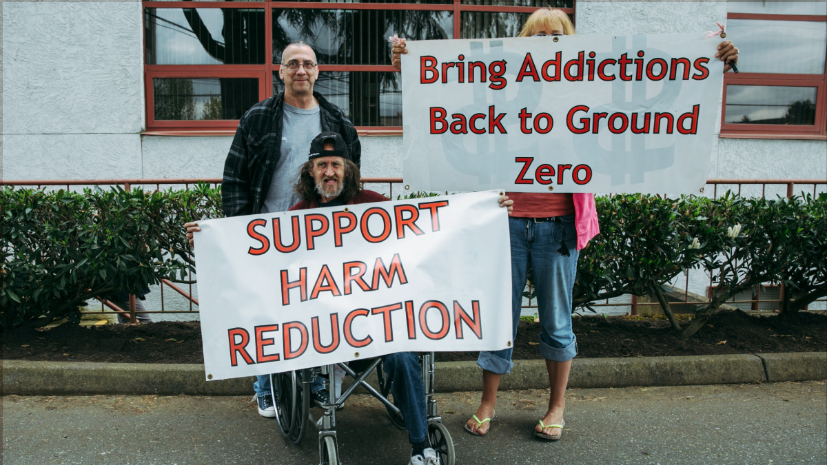 """Three people gathered together holding white signs with red lettering on a sidewalk. One person uses a wheelchair and holds a banner that says """"Support Harm Reduction"""". Another person stands behind him. The third person is holding a banner that says """"Bring Addictions Back to Ground Zero"""" The sign is covering their face and upper body"""