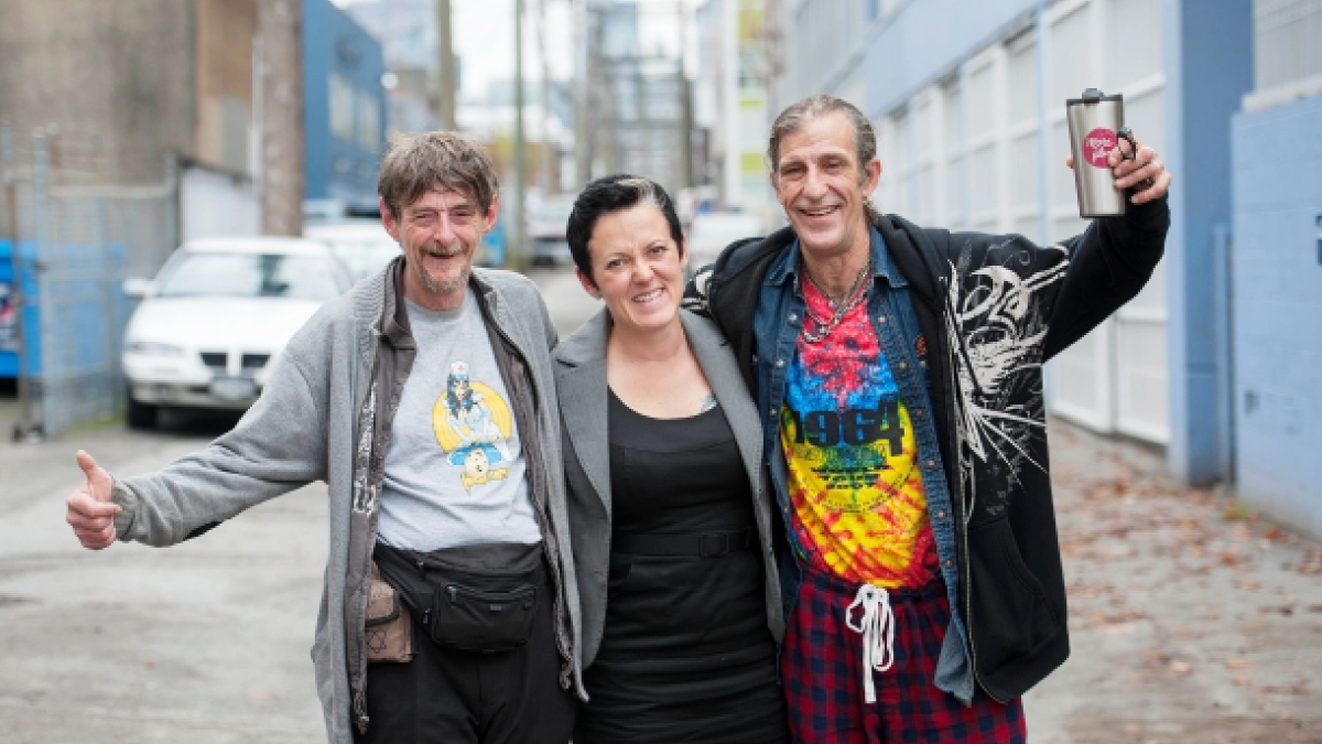 Three people are standing together in an alley facing the camera with big smiles in celebration and holding each other.