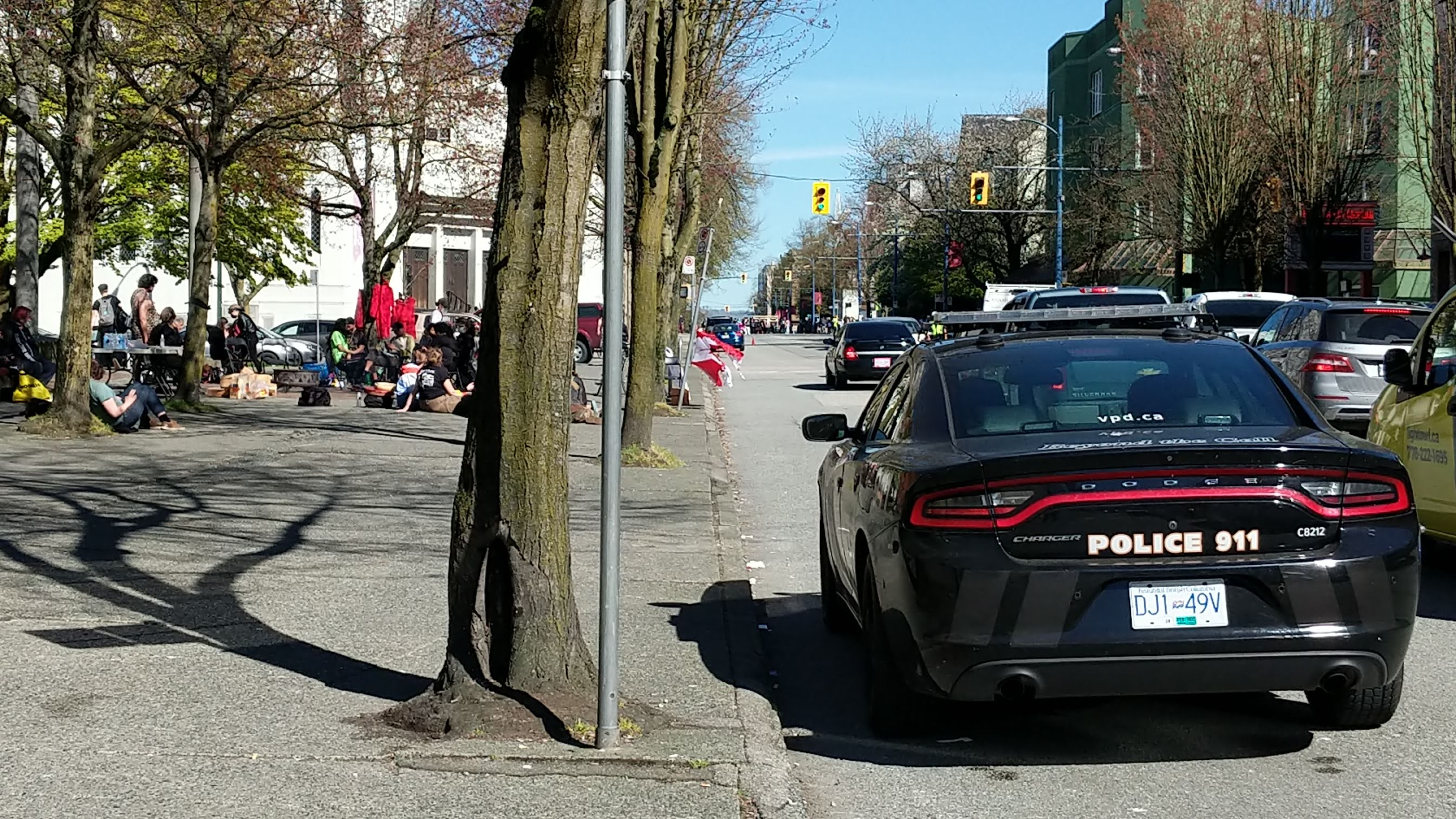 Vancouver POlice Department car parked on a street in Vancouver's Downtown Eastside. A group of people are gathered in a large area off the sidewalk.