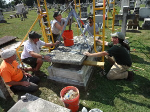Instructors Jason Church and Moss Rudley work with participants to reset a grave ledger. Image provided by Jason Church.