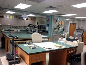 Photo showing part of the Conservation Lab, including the microscope, fume hood, document washing sink, non-aqueous spray deacidification booth, oversized work table with built-in light table, and one of four individual work benches. Photos courtesy of Melissa Tedone and the Iowa State University Library and Archives.