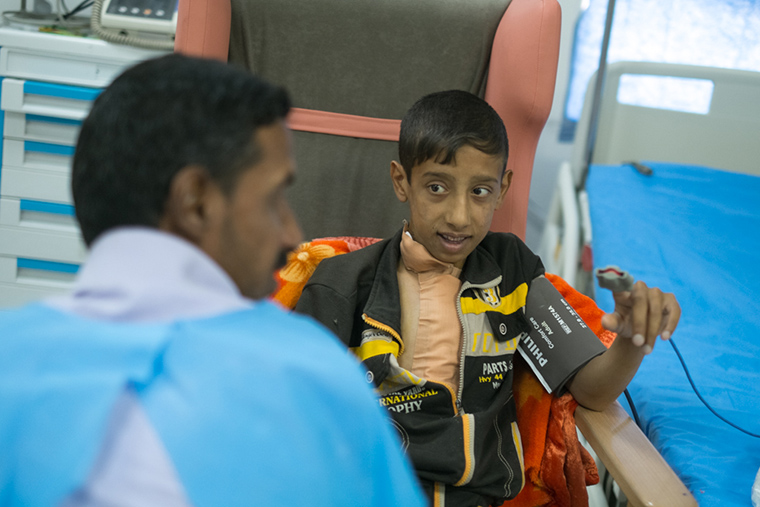 Ali and his father sit together after Ali's lifesaving heart surgery.