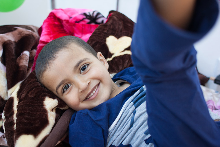Young Hamam lays on his hospital bed, waiting for his lifesaving heart surgery. He has a big smile and his eyes sparkle.