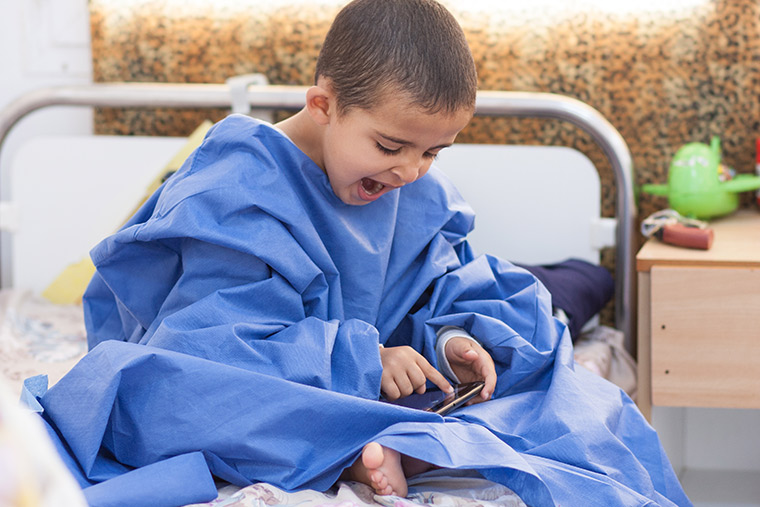 Hamam sits on his hospital bed, wrapped in a sterile gown, and yawning while playing a video game. Waiting for heart surgery is hard work!