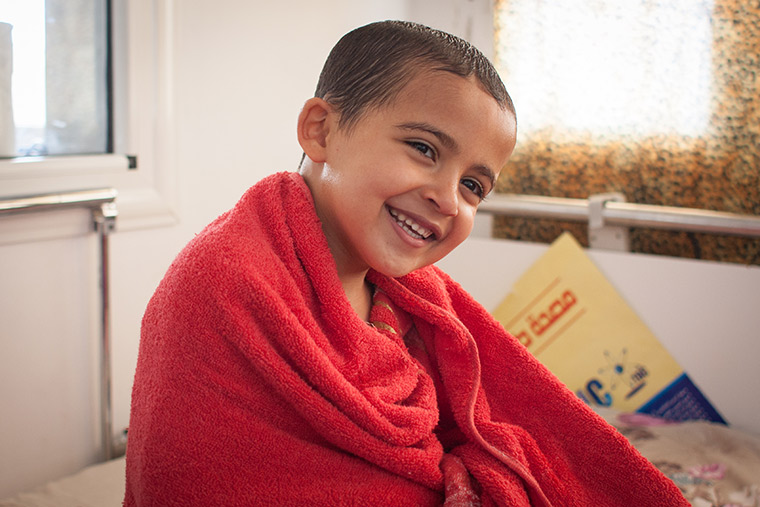 Young Hamam is wrapped up in a red towel, smiling. He just had a bath before his lifesaving heart surgery.