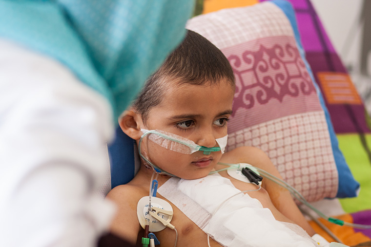 While Hamam's mom gets a little rest, a friend sits with her son after heart surgery.