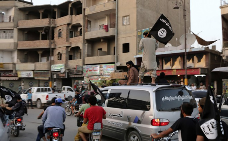 Members of ISIS (ISIL or Islamic State) ride through the streets of Samarra Iraq, carrying their flags.