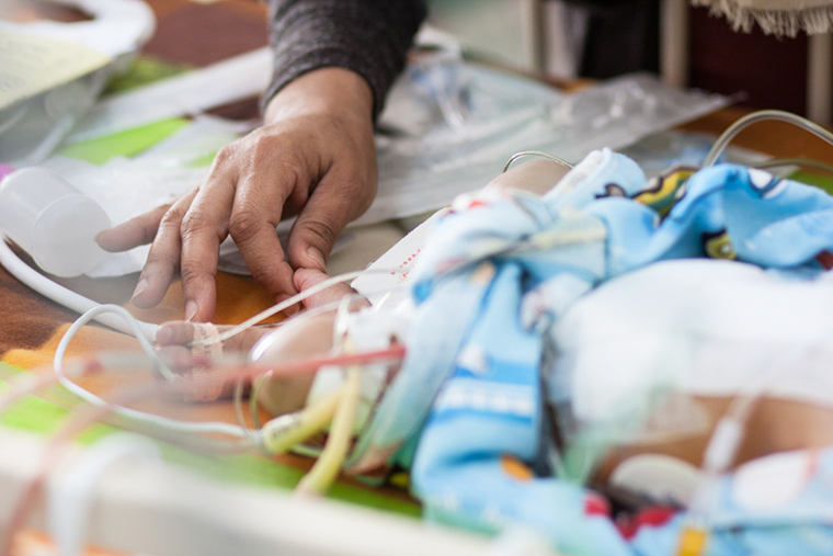 Norea's mom touches her toes tenderly, following her daughter's lifesaving heart surgery in Libya.