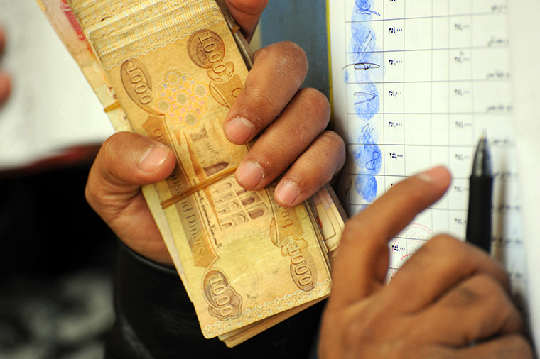 A handful of dinars being paid out to employees.