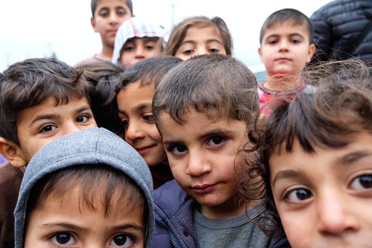 Displaced children in Iraq, Shabaks from Sinjar, gather under a grey sky.