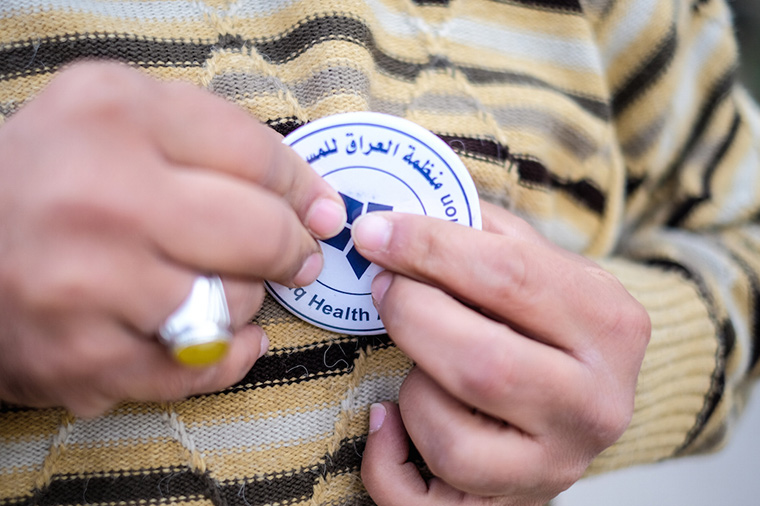 A volunteer with our partner organization Iraq Health Aid Organization, pins an identifying button on their shirt.