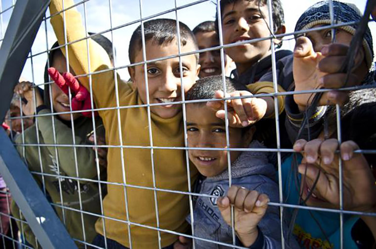 Children grip the chain-link perimeter fence around the Laylan Camp for displaced persons, outside of Kirkuk, Iraq.