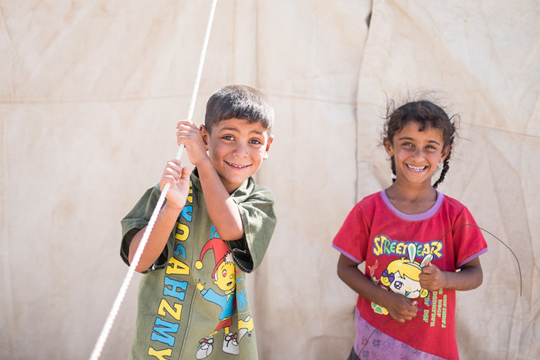 A boy and girl play outside their tent, their temporary home since being driven out by ISIS in the Anbar Province.