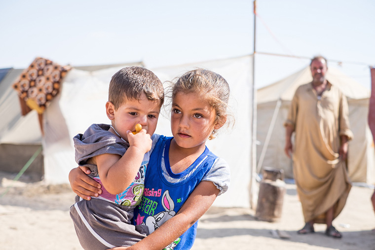 Displaced kids do their best to deal with the heat as we deliver relief aid to their families. They are camped in the dessert, 3 miles from the front line with ISIS.