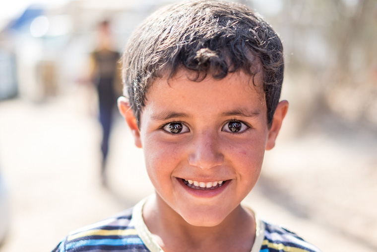 A young, bright-eyed boy poses with a smile. His family are displaced, camped out in the Iraqi desert, and in need of aid.
