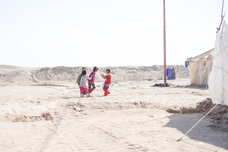 Children play in the desert, beside their temporary tent-homes, after being displaced by ISIS in Iraq.