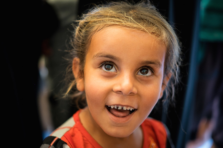 A young girl seen by a doctor during a relief aid drop. She smiles wide, revealing that her front teeth are black with cavities.