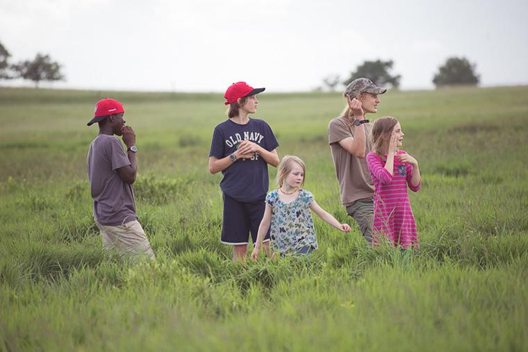 Ginny Sheller's children, standing in tall prairie grass.