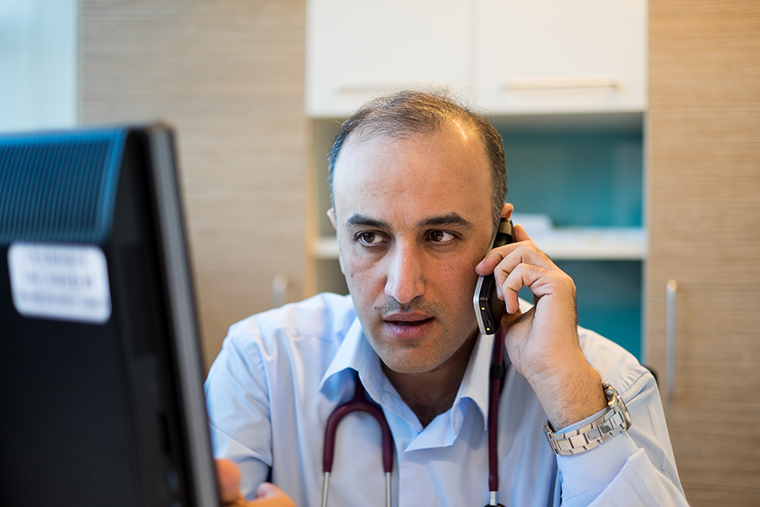 Dr. Firas on the phone with parents of his young patients, Faruq Medical Center, Iraq.