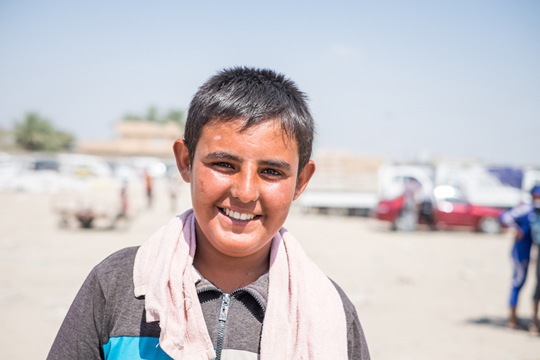 One of the boys who makes his living hauling cargo to displaced families, across the Bzebez bridge, Iraq. The heat was unbearable, he is red-faced and sweaty, but still smiles.