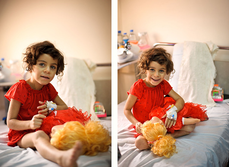 Deeya sits on her hospital bed in a red nightgown. Her lifesaving heart surgery made everything possible, even school.