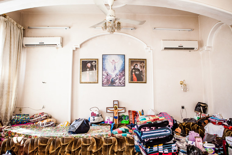 Christian iconography mixes with the belongings of displaced Assyrians at a Chaldean church in Iraq.