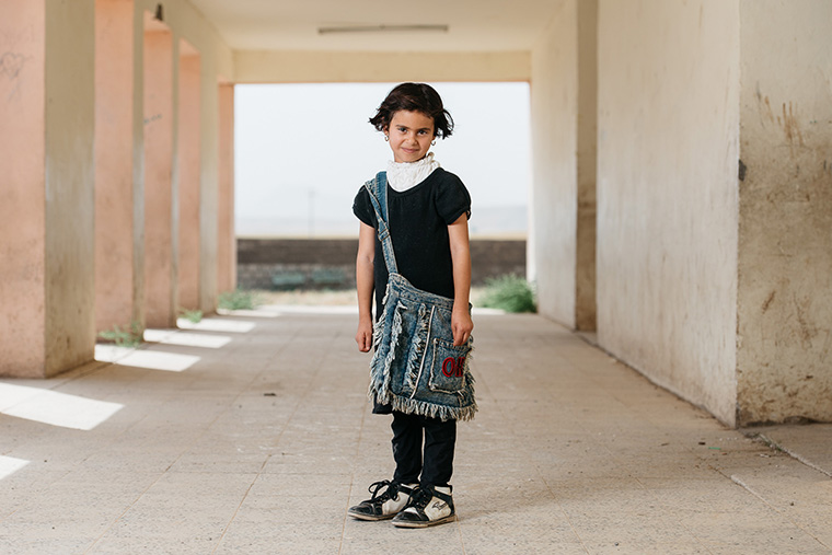 A young girl stands ready and confident to start school. Being displaced hasn't dampened her desire to learn!