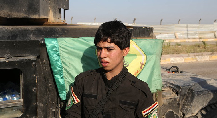 In a photo from March 2015, a young Shiite volunteer militiaman stands near a vehicle on his way to the battlefield against ISIS in Tikrit, Iraq. (AP Photo/Khalid Mohammed)