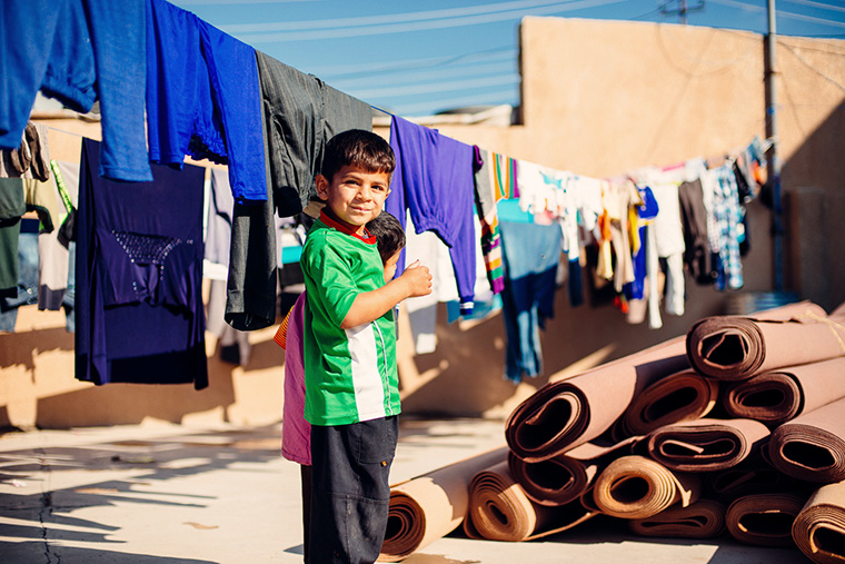 Young children, displaced by war in Iraq, play amongst rolls of carpet.