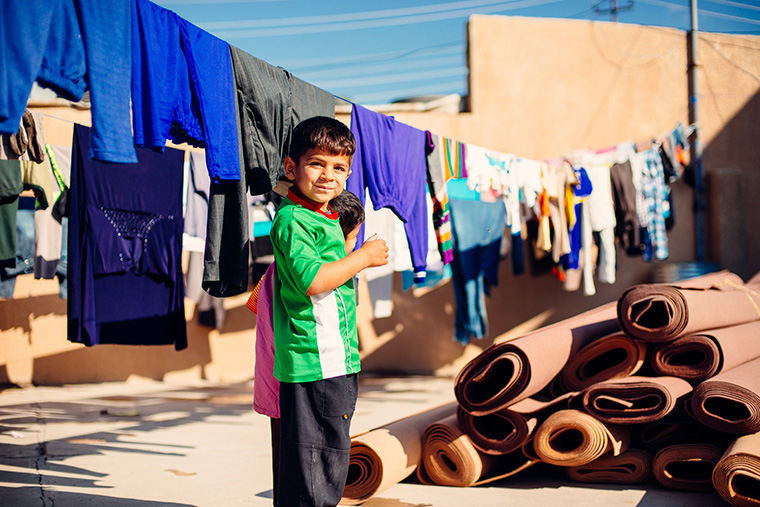Laundry hangs in what used to be a school playground. Displaced Iraqi families have made this school home for the last year, after being driven out of their own homes by ISIS.