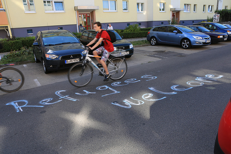 The message 'refugees welcome' is written in large chalk letters on the side of a road.