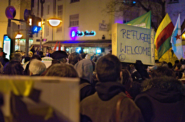 At an evening street protest, a message is marked out onto the side of a cardboard box—refugees welcome.