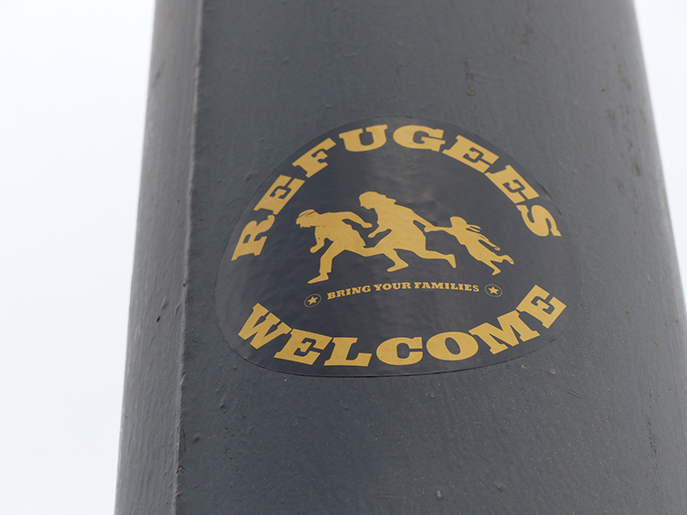 Stickers are being plastered on light poles in Germany, welcoming refugees.