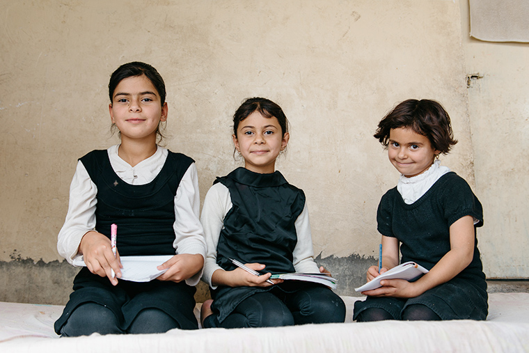 Young girls displaced by ISIS work on their homework after class.
