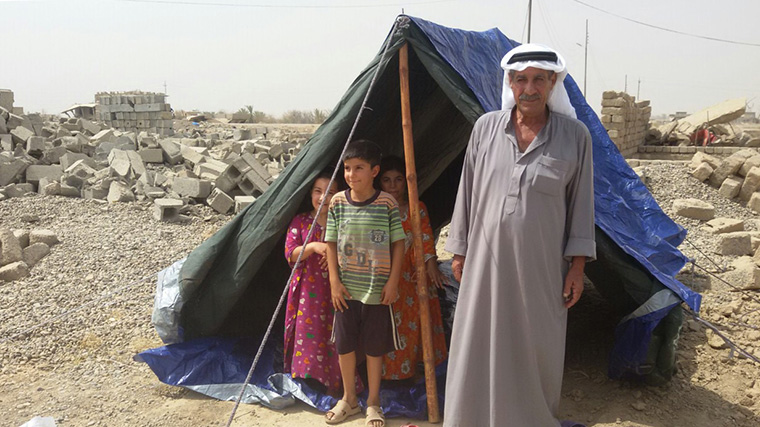 An Iraqi man and young children stand at the entrance of their new tent.