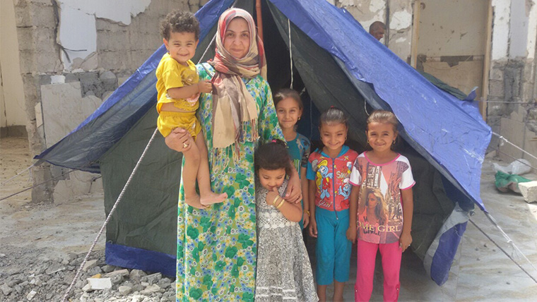 A mom and her young children stand at the entrance of their new tent. The mother smiles—she now has shelter for her children.