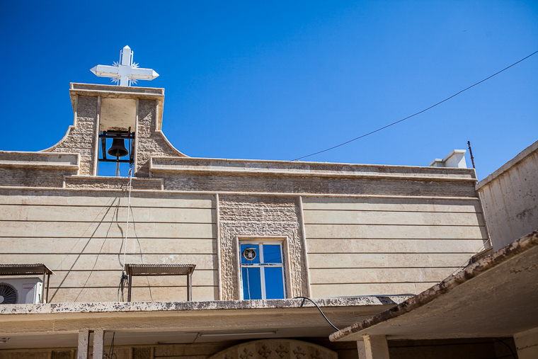 The cross, a well-known symbol of Christianity, is mounted high on a church in Iraq.