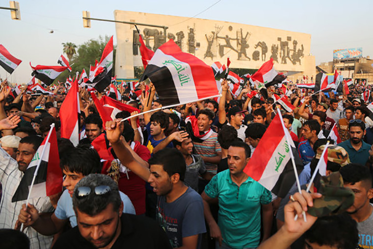 Protesters fill Baghdad's Tahrir Square, holding banners and demanding change from the government.