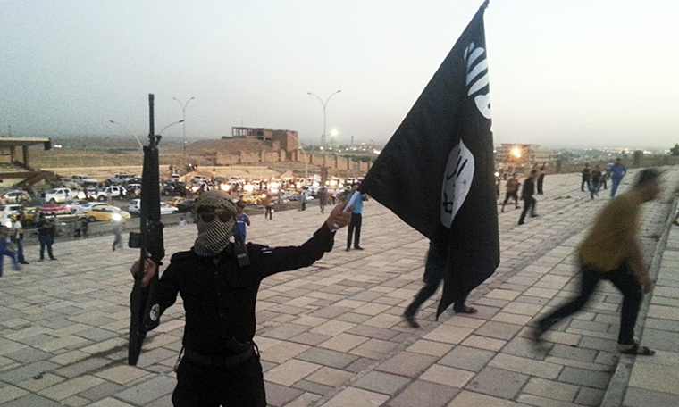 A member of ISIS waves the symbolic black flag in one hand and a gun in the other, in Mosul, Iraq.