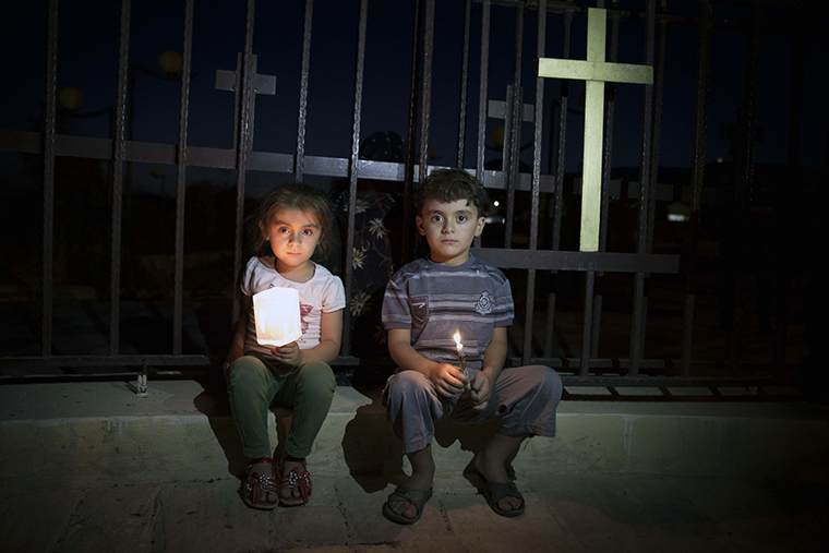 Two Assyrian children sit beside a church yard fence prominently displaying a cross. It is night. The children, displaced from Mosul by ISIS, hold candles.
