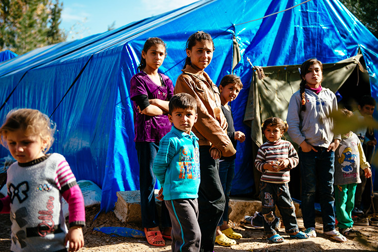 A group of Yazidi families, driven from their homes by ISIS, now live in blue-tarp tents.